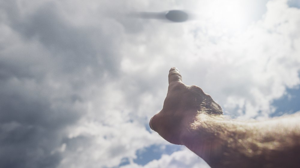 A hand pointing to a UFO