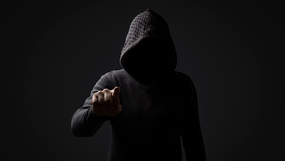 threatening figure wearing black hood