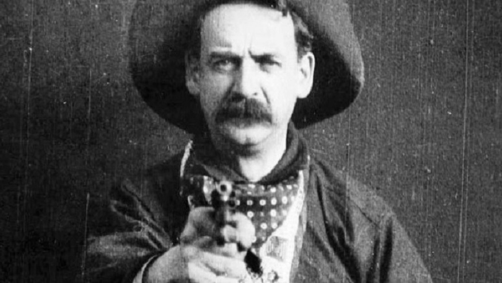 photo of robber with hat holding a gun out