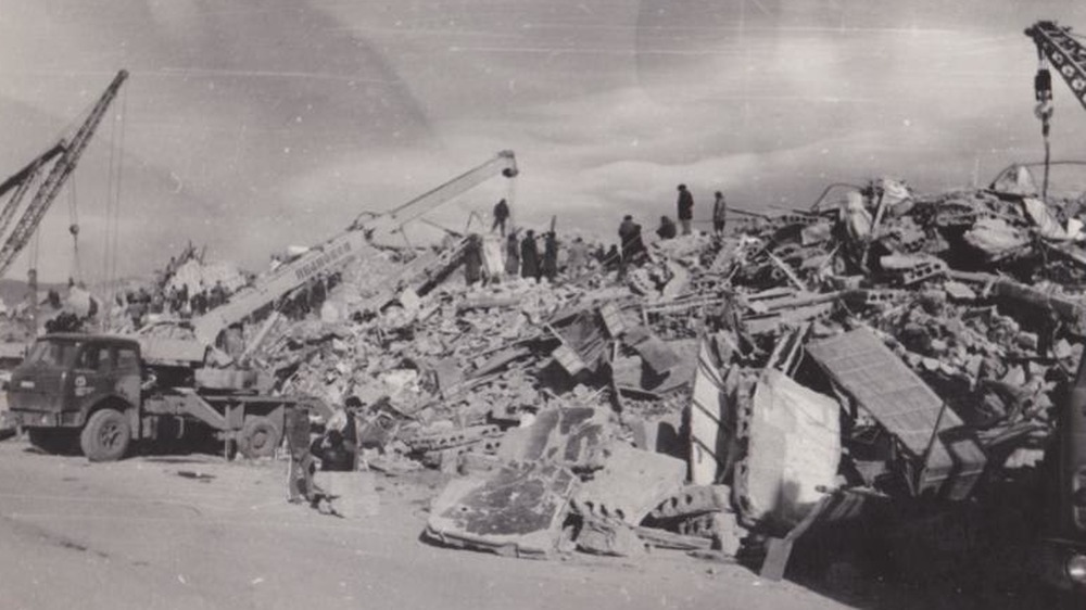 People standing atop rubble in aftermath of the earthquake